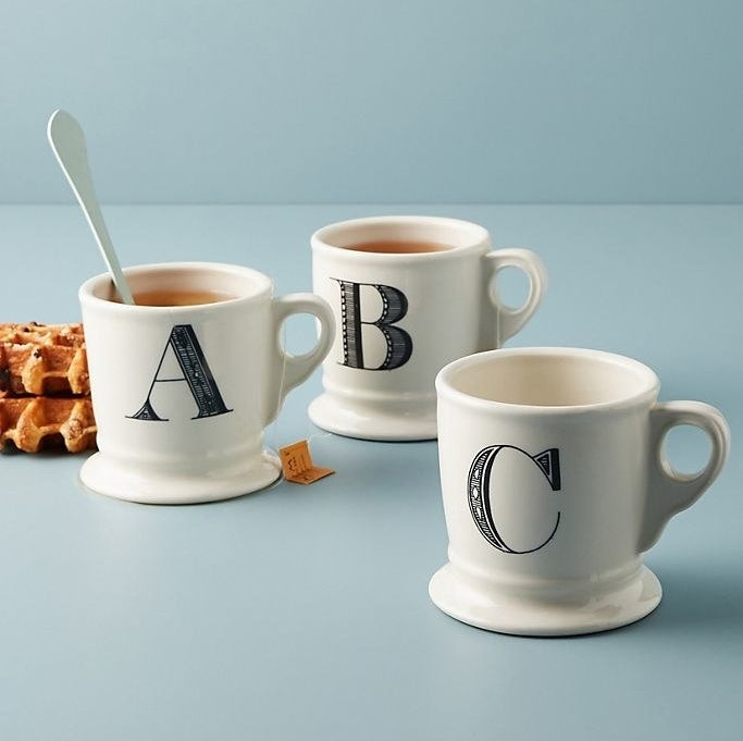 The A, B, and C mugs in white with black serif lettering