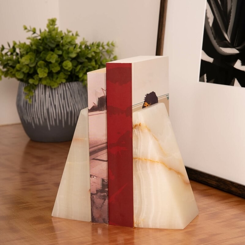 white, beige, and orange marble bookends holding books on a counter in front of a plant and photo