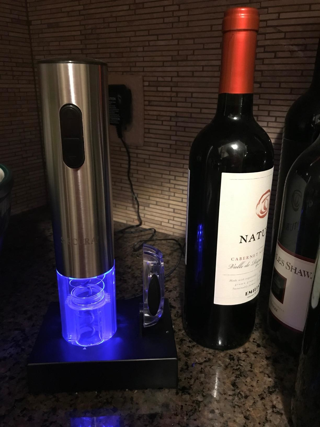 A reviewer's wine opener displayed upright next to a bottle of wine on a kitchen counter