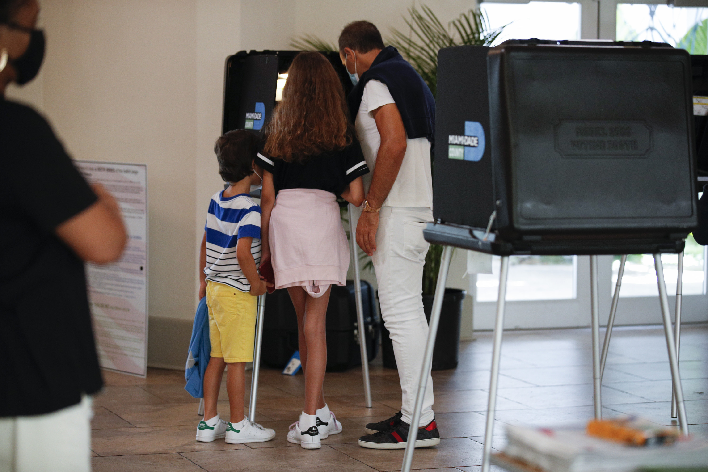 Family huddles around ballot at a voting location.