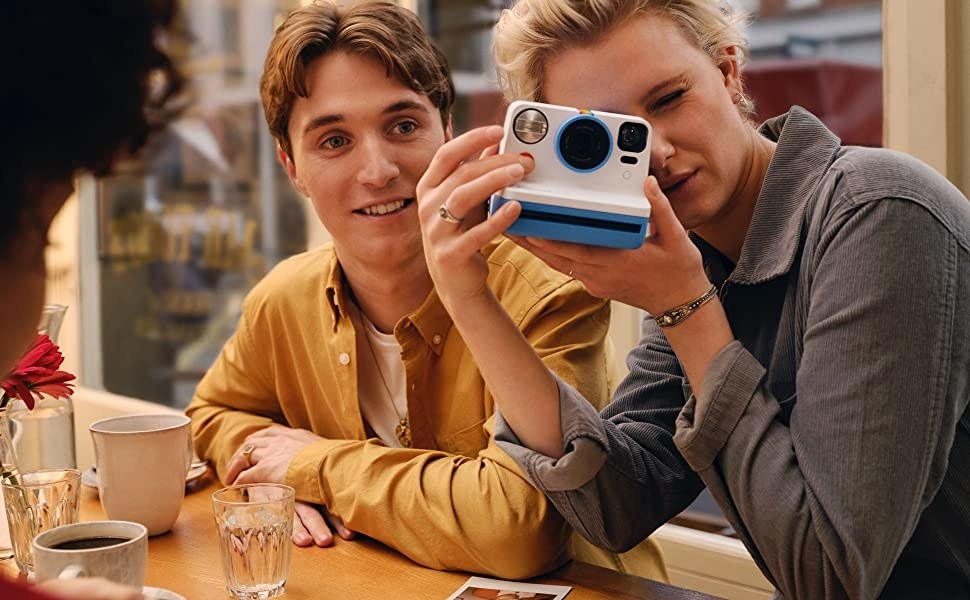 a model takes a picture with the polaroid camera