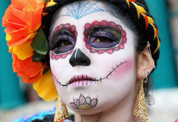 A woman with her face painted as a skull and her braided hair adorned with flowers for Día de los Muertos