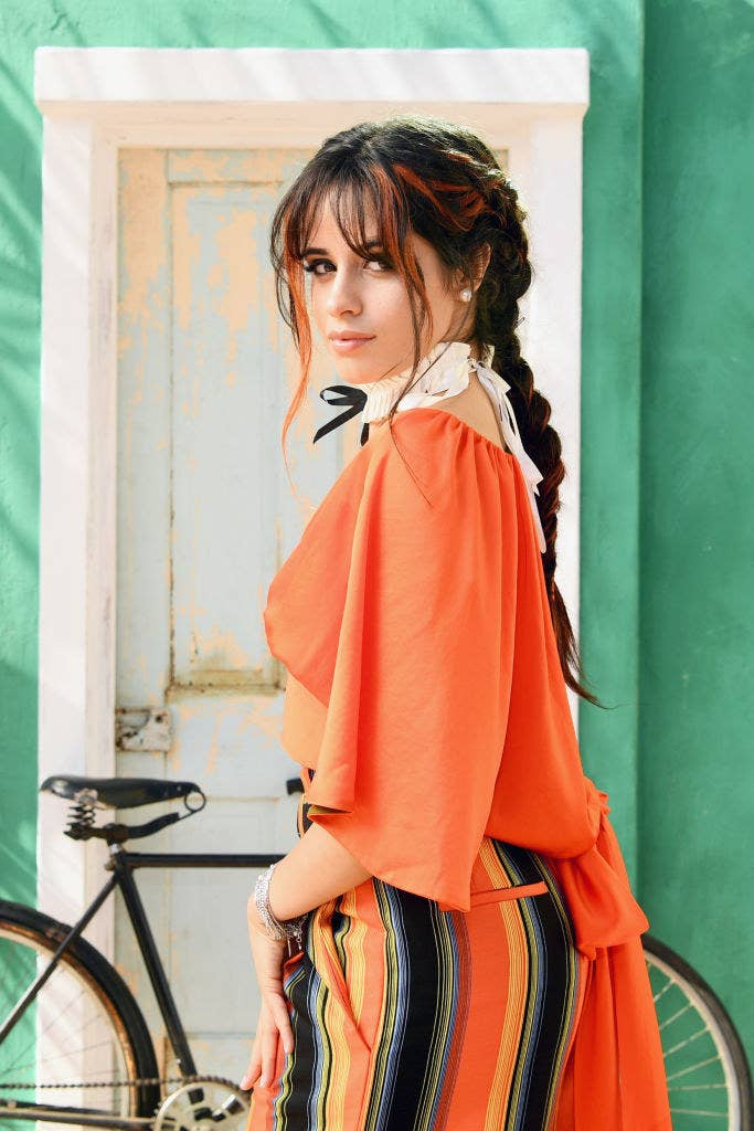 Camila with her hair in two braids standing in front of a bicycle that's leaning against a door