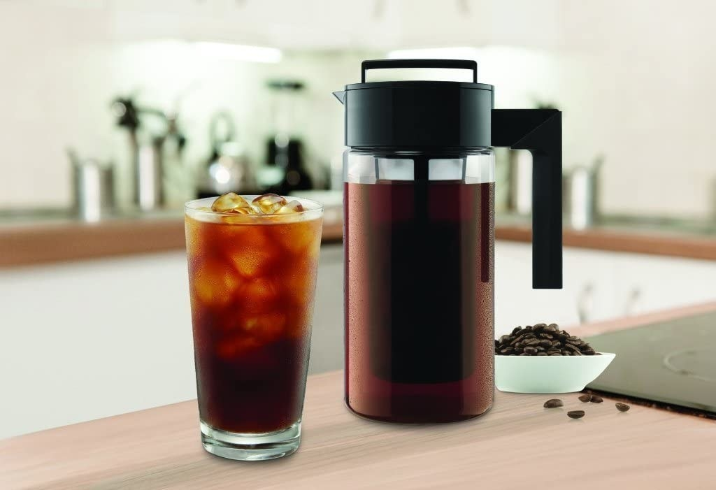 A cold brew maker on a kitchen counter next to a glass filled with iced coffee and a small bowl of coffee beans