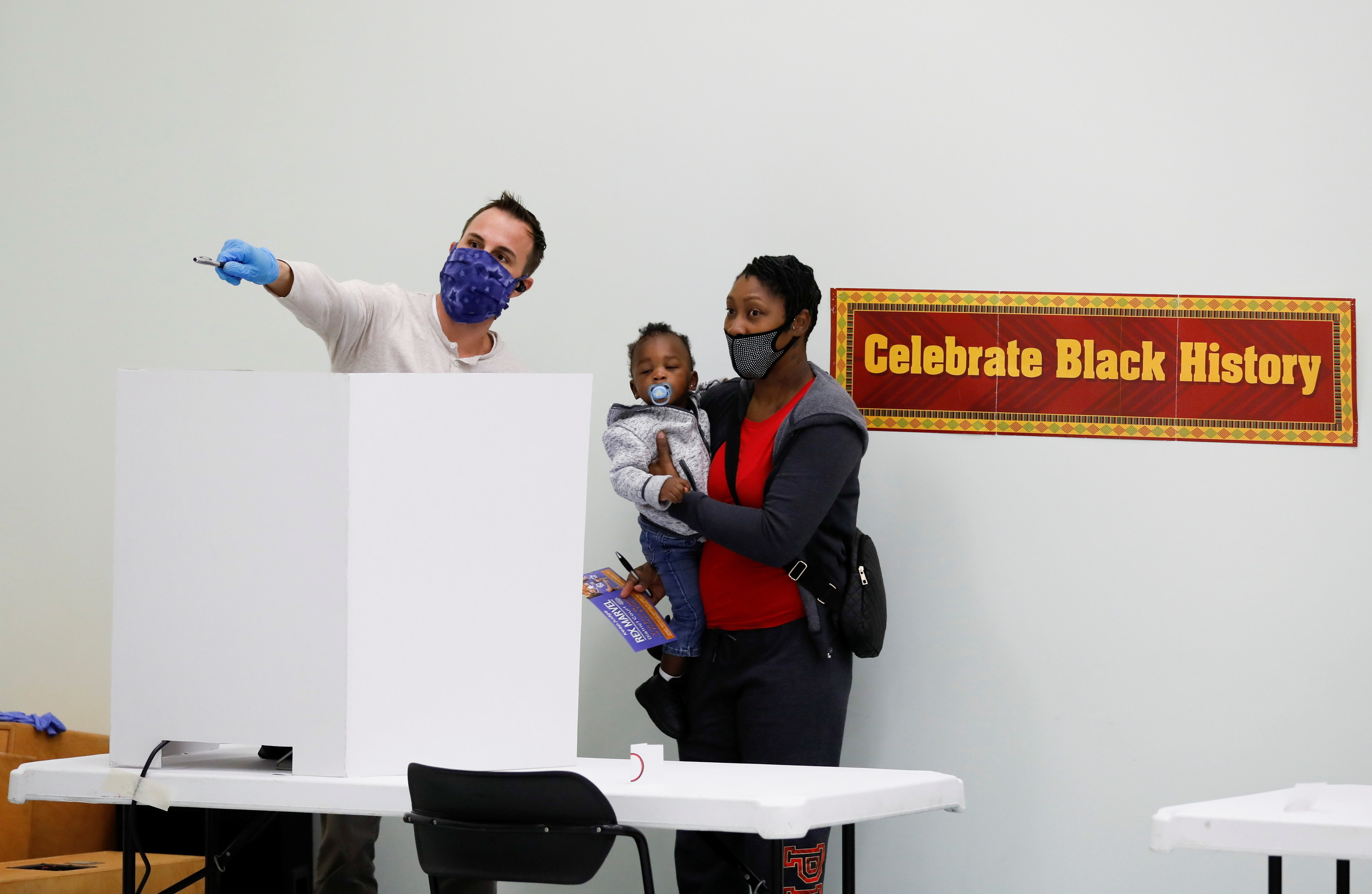 Man pointing and mother holding her baby at a polling place.