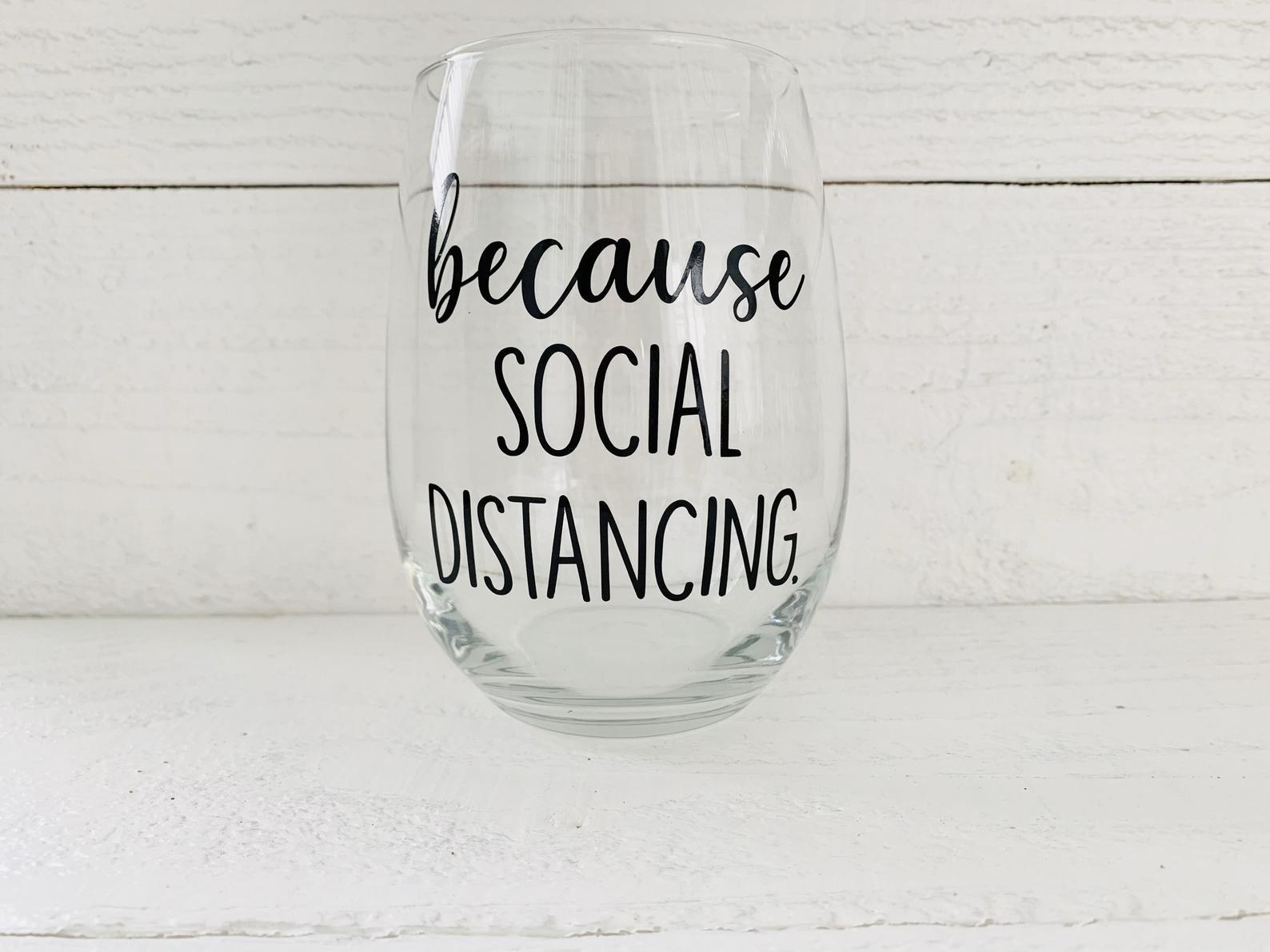 """the stemless glass which says """"because social distancing"""" on it"""