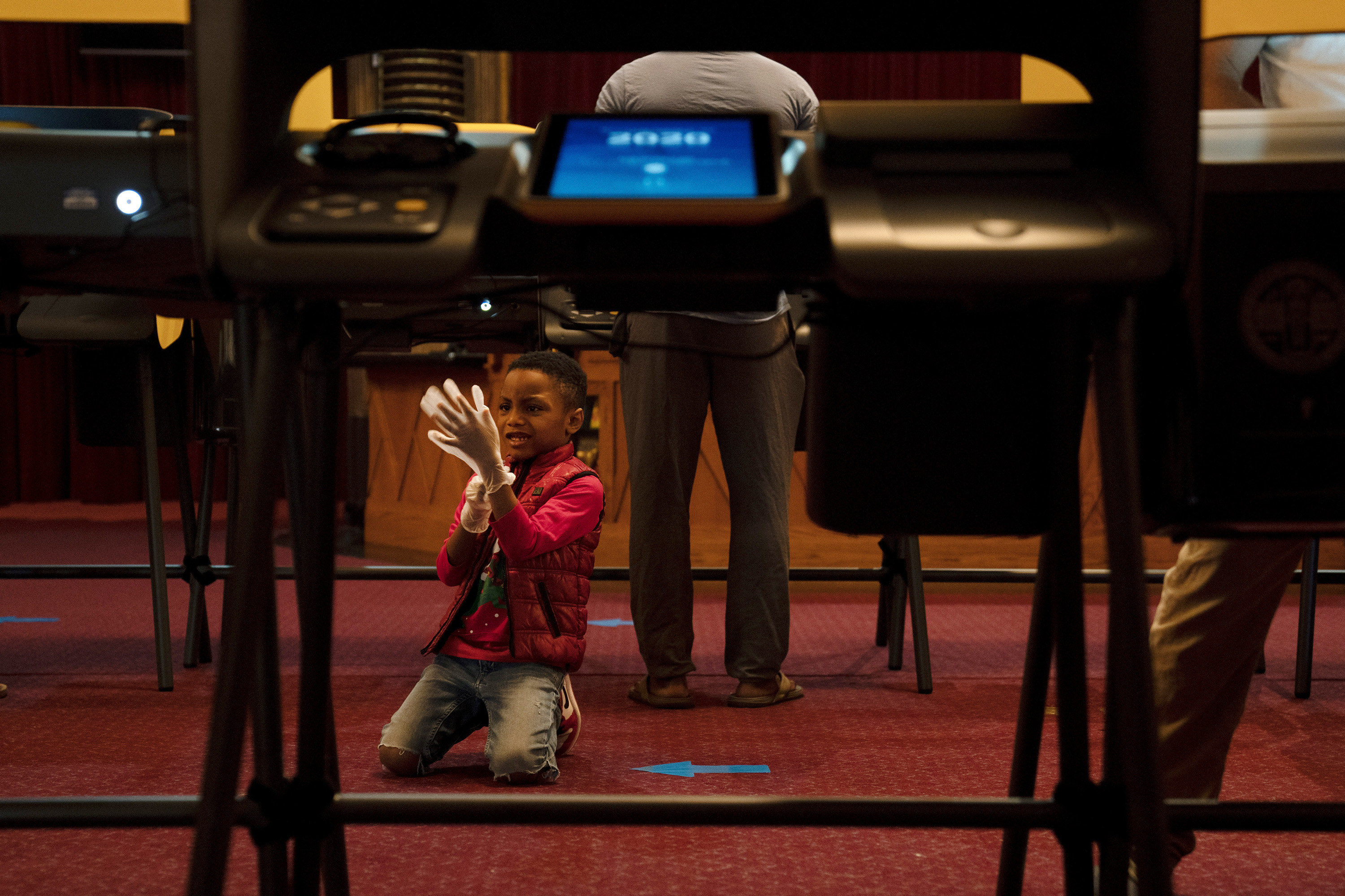 Boy with plastic glove on the floor of a polling place.
