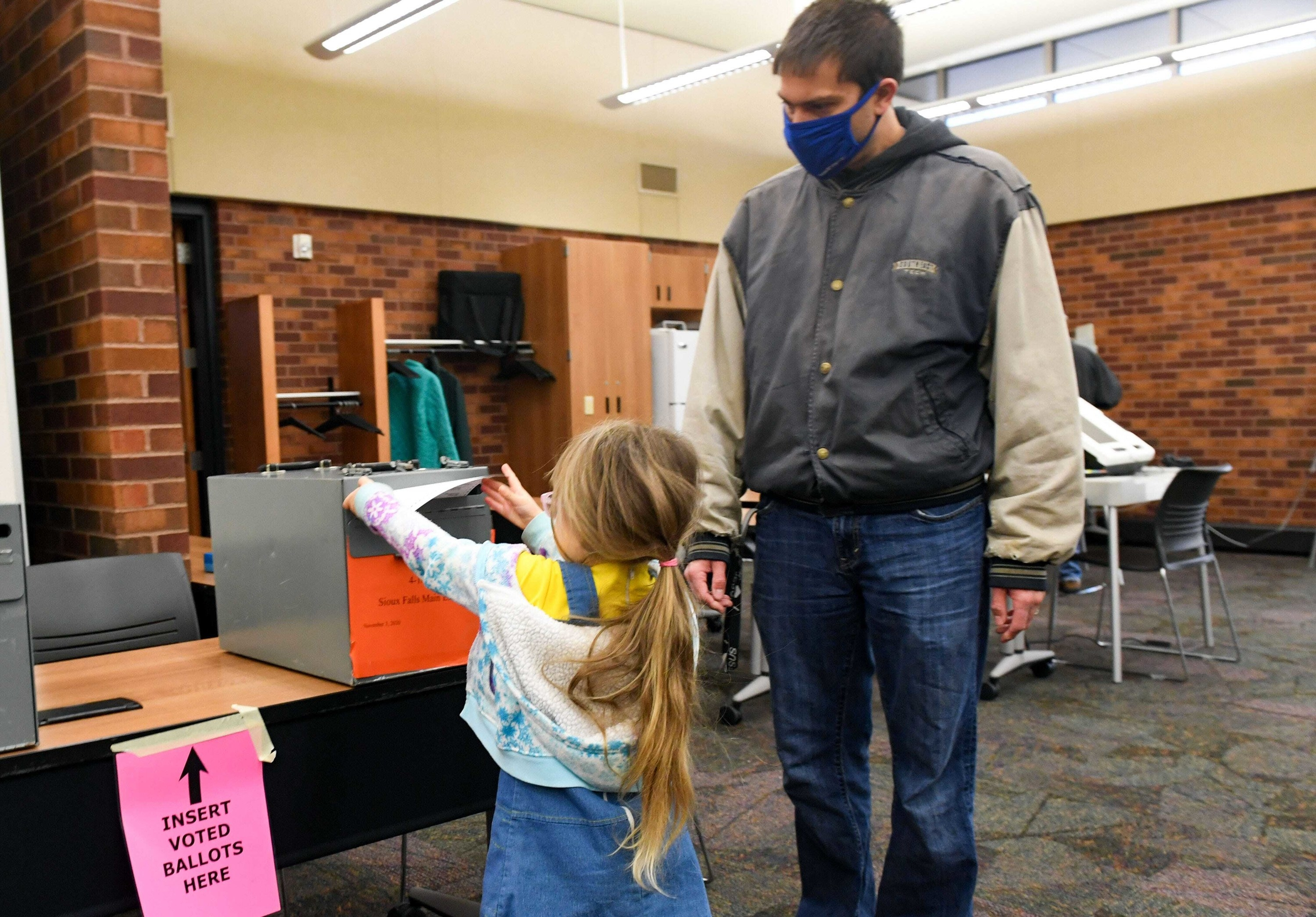 Young girl with ponytail helping her father vote.