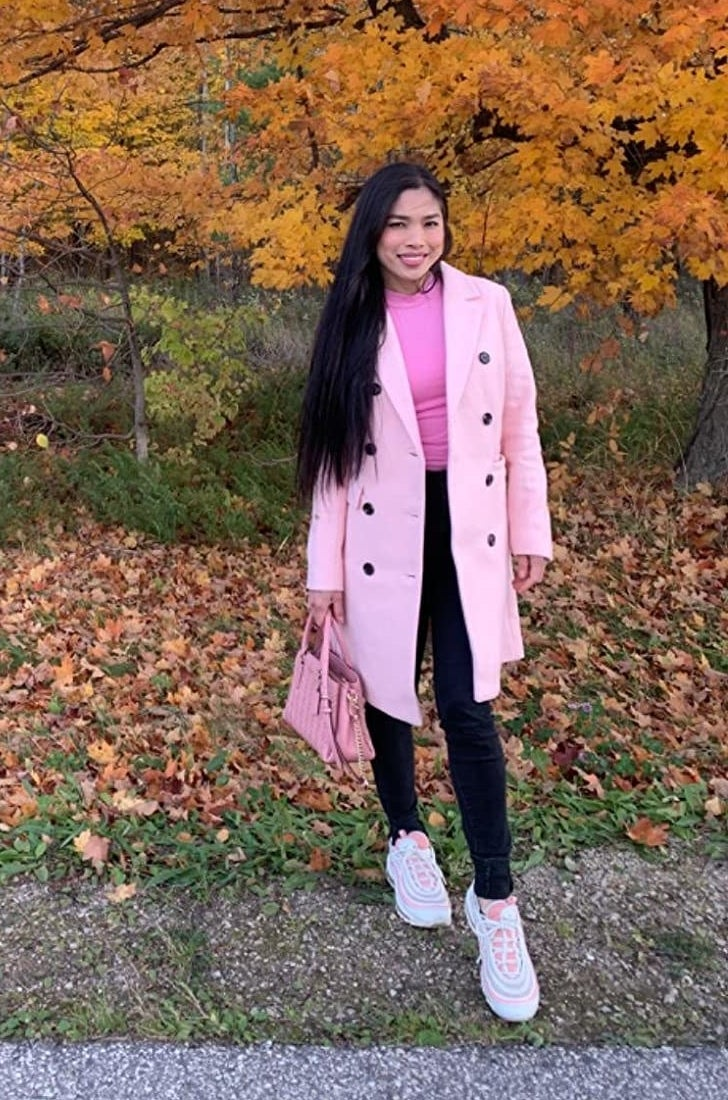 Reviewer wearing the coat in pink with black buttons open