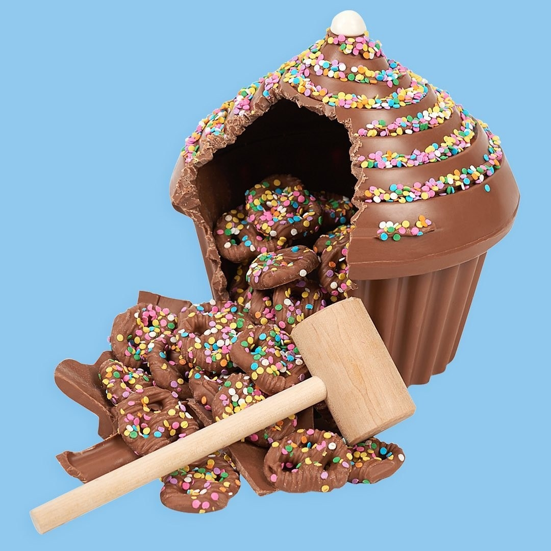 A giant cupcake made out of hollowed chocolate that's broken apart to reveal it's filled with chocolate pretzels