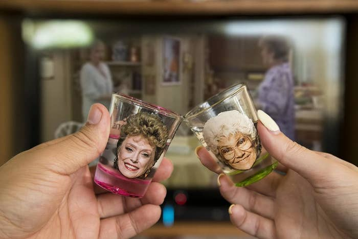 Two people cheersing with shot glasses that have Blance and Sofia's face