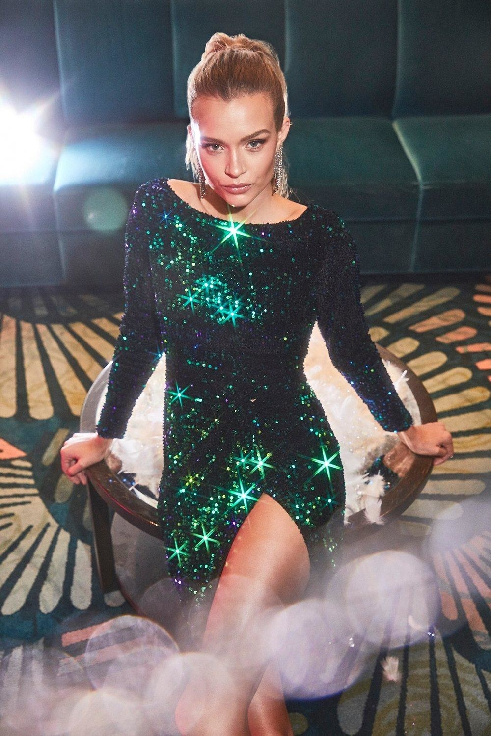 Model wearing green sequin dress and sitting on a table