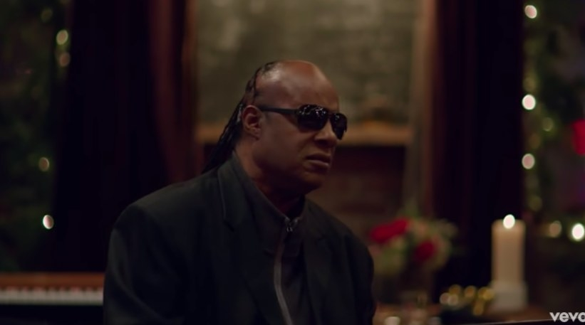 Stevie Wonder sits in a room decorated for Christmas