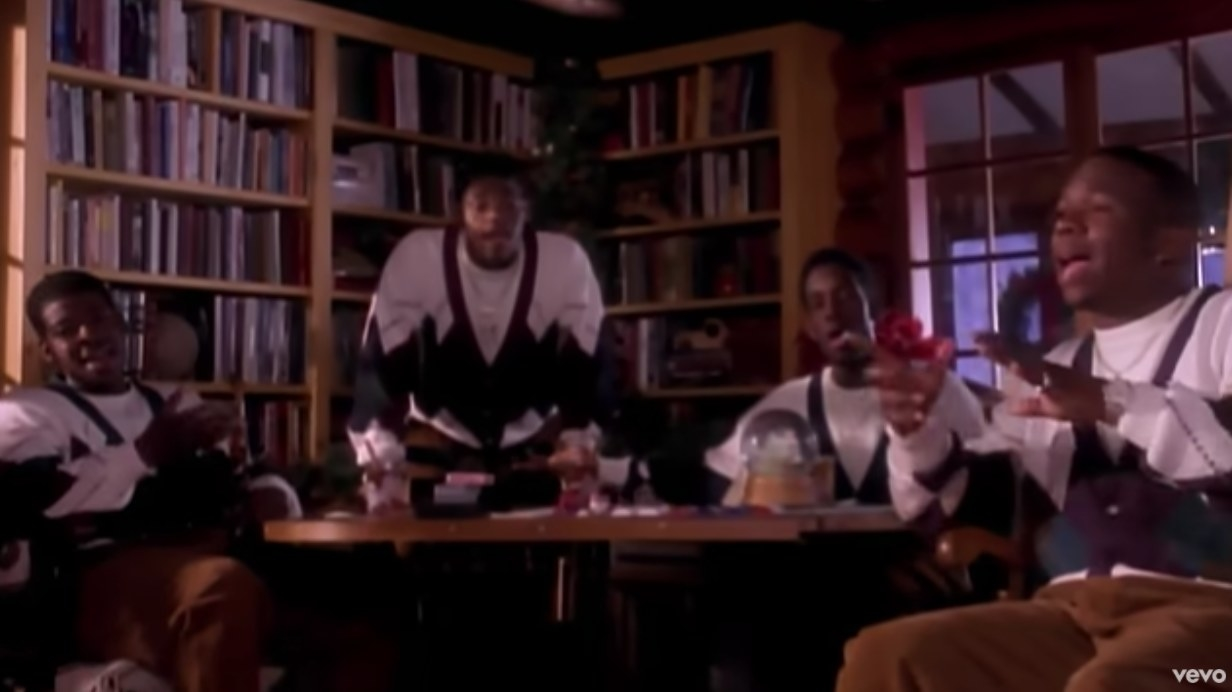 Boyz II Men wear matching Christmas cardigans and sing while sitting around a table in front of a bookshelf