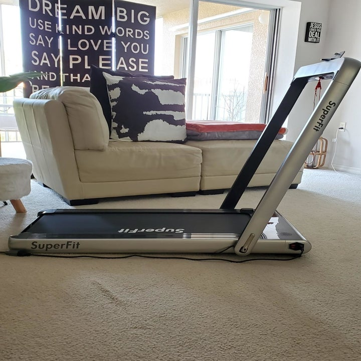 reviewer shows same black treadmill with riser up in their living room