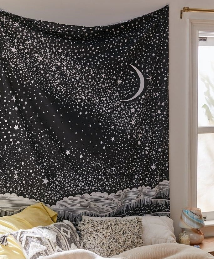 black tapestry with a white crescent moon and several white stars hanging above a bed