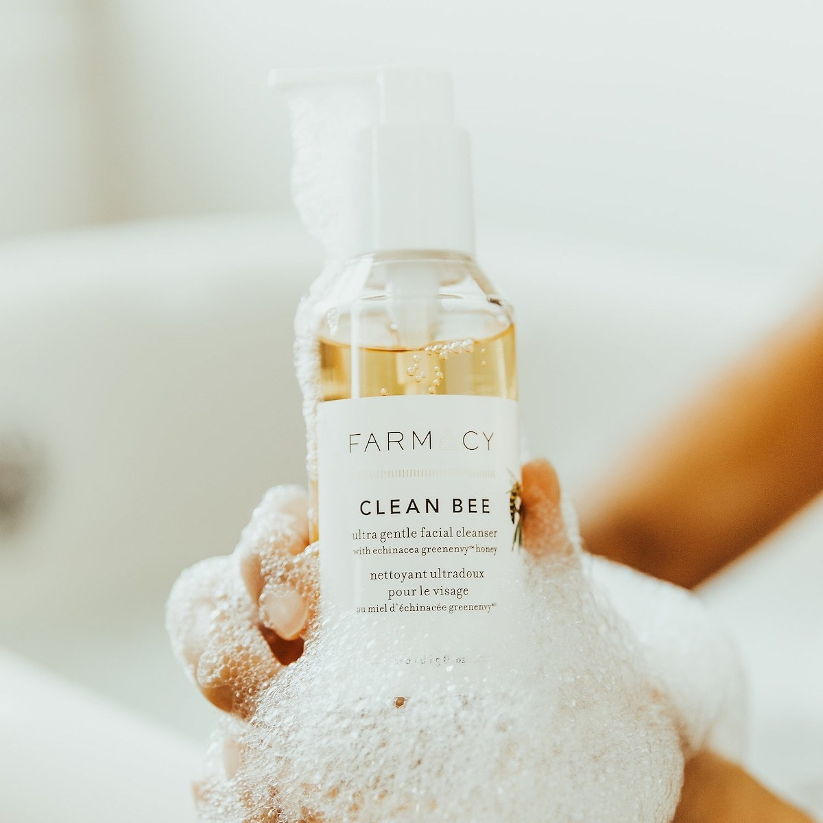 The bottle of cleanser, covered in suds, being held up by a Model in a bath tub