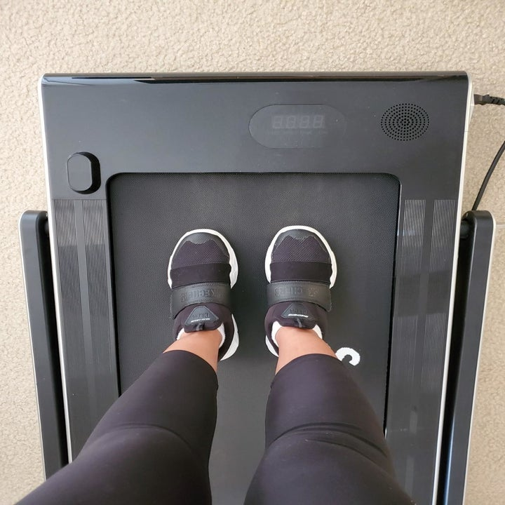 reviewer places feet on black treadmill with the riser down