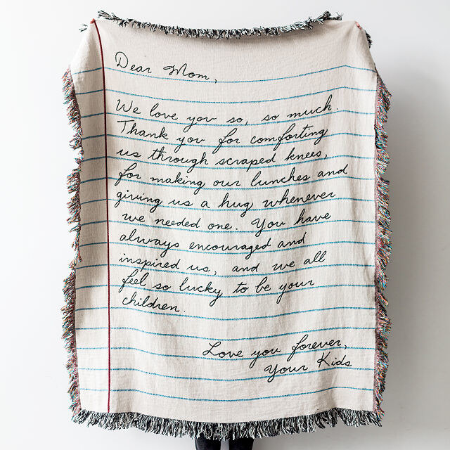 Tasseled throw blanket designed to look like a piece of paper, with handwritten letter on front