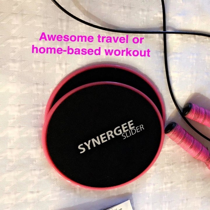 """Reviewer's photo of two pink and black core sliders and a pink jump rope on the floor that says """"awesome travel or home-based workout"""""""