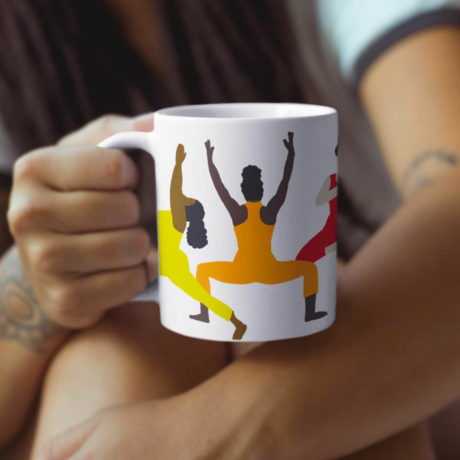 model's hand holding a mug with animated brown-skinned people in bright workout clothes doing yoga poses