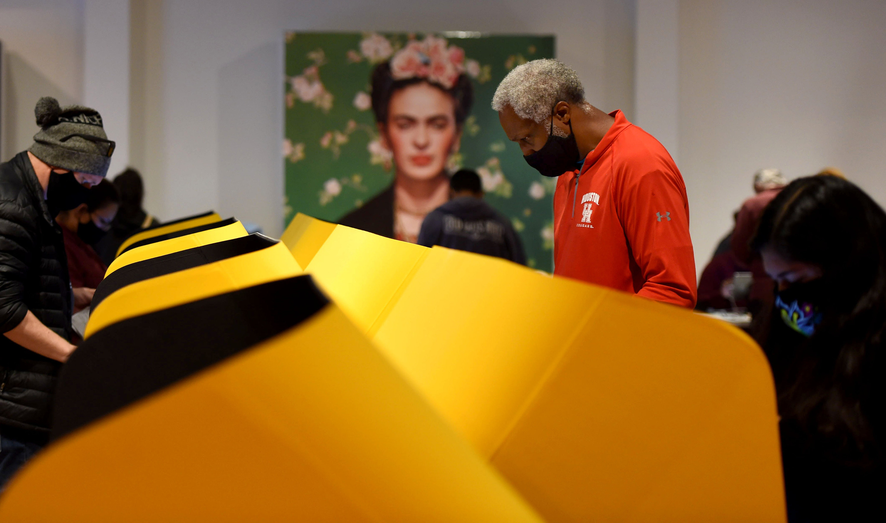 Man voting in front of a portrait of Frida Kahlo.