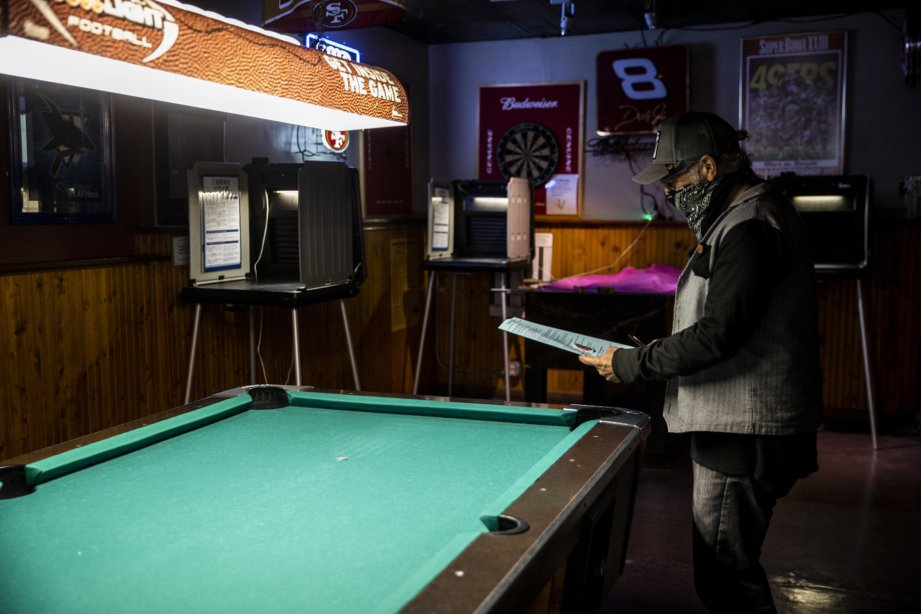 Man reviewing his ballot in front of a pool table.