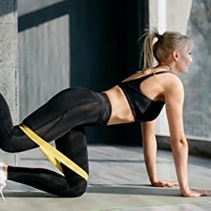 Model uses yellow resistance band to do leg lifts