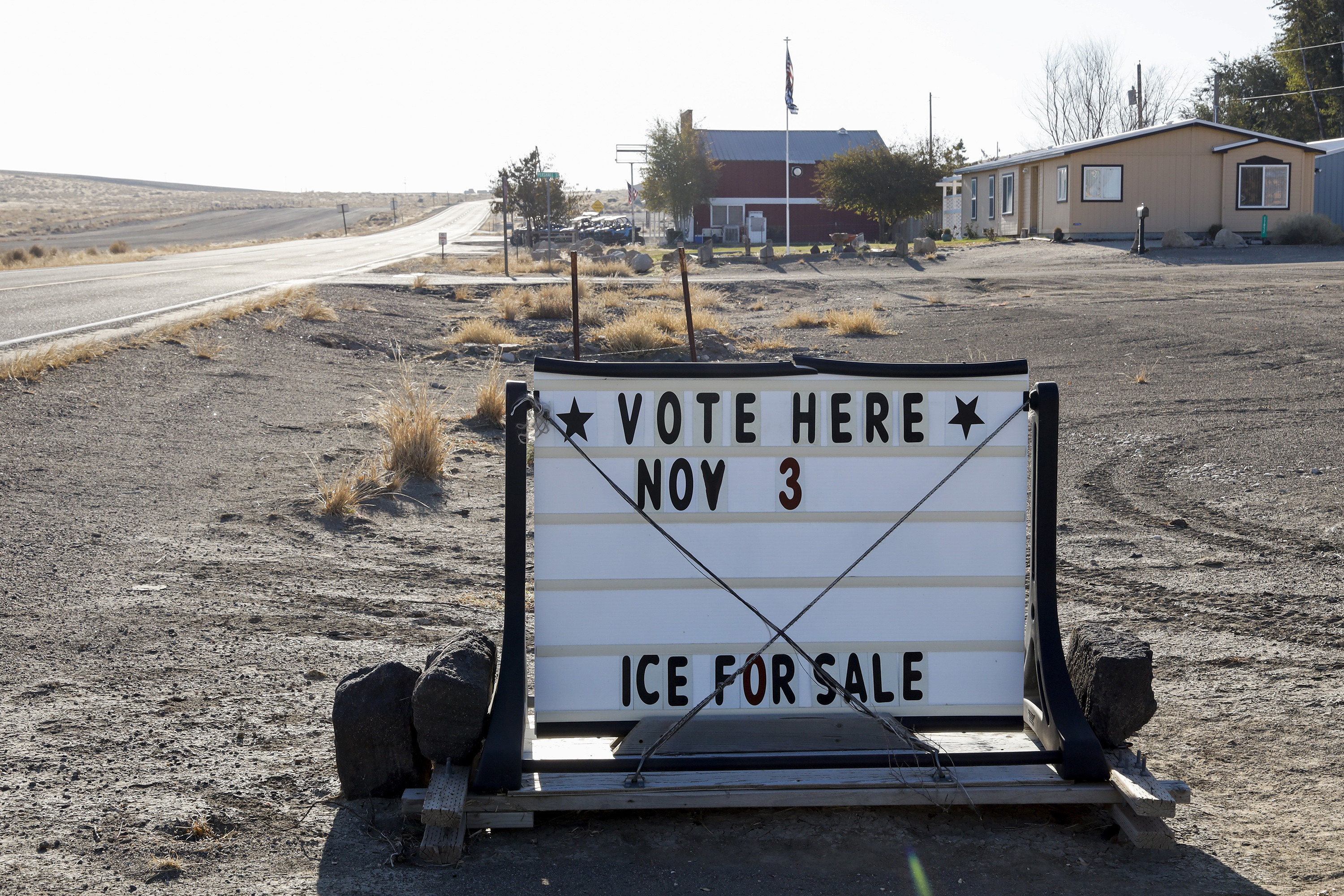 A sign advertising voting on the side of a dusty road.