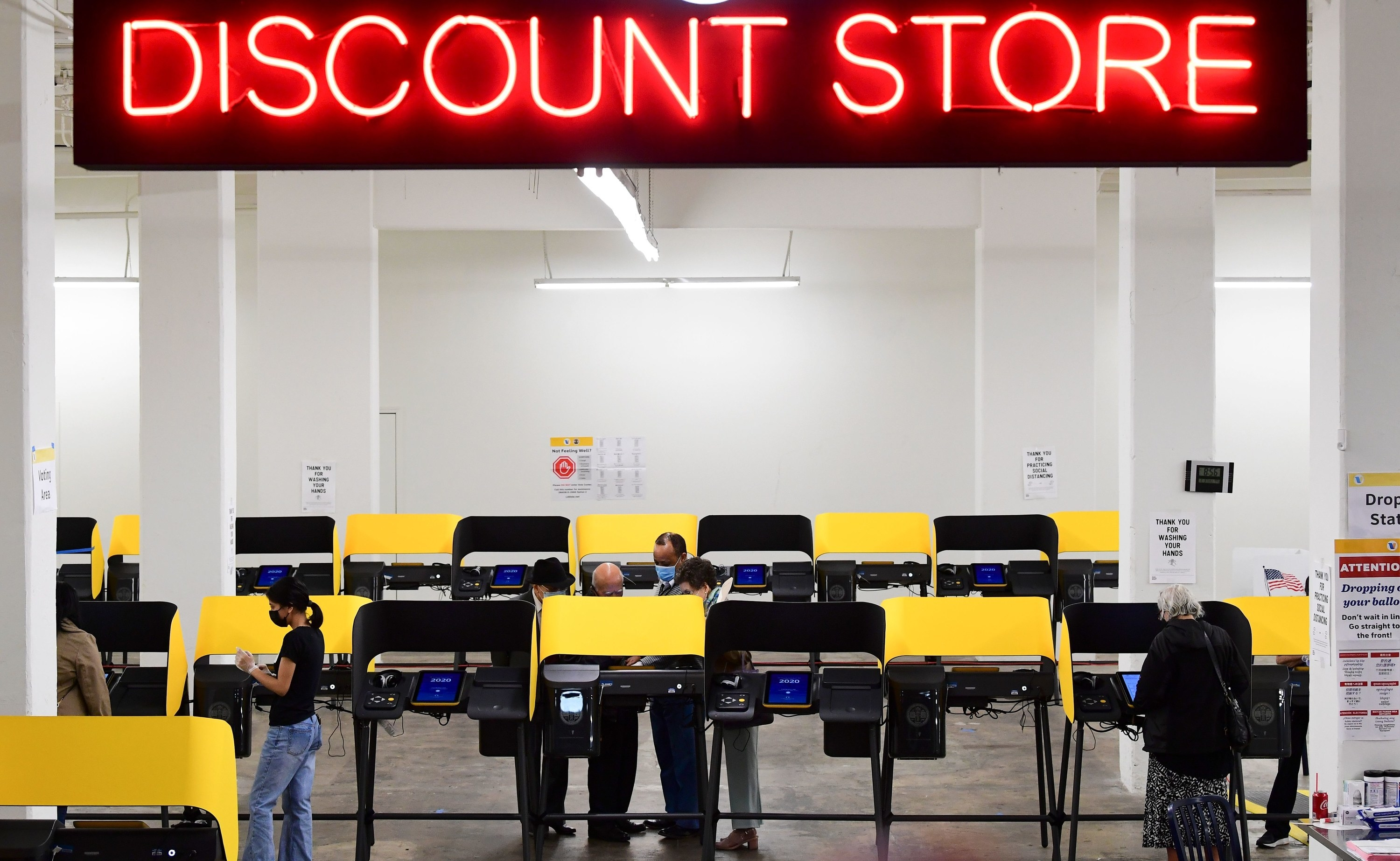 People voting underneath a giant discount sign.