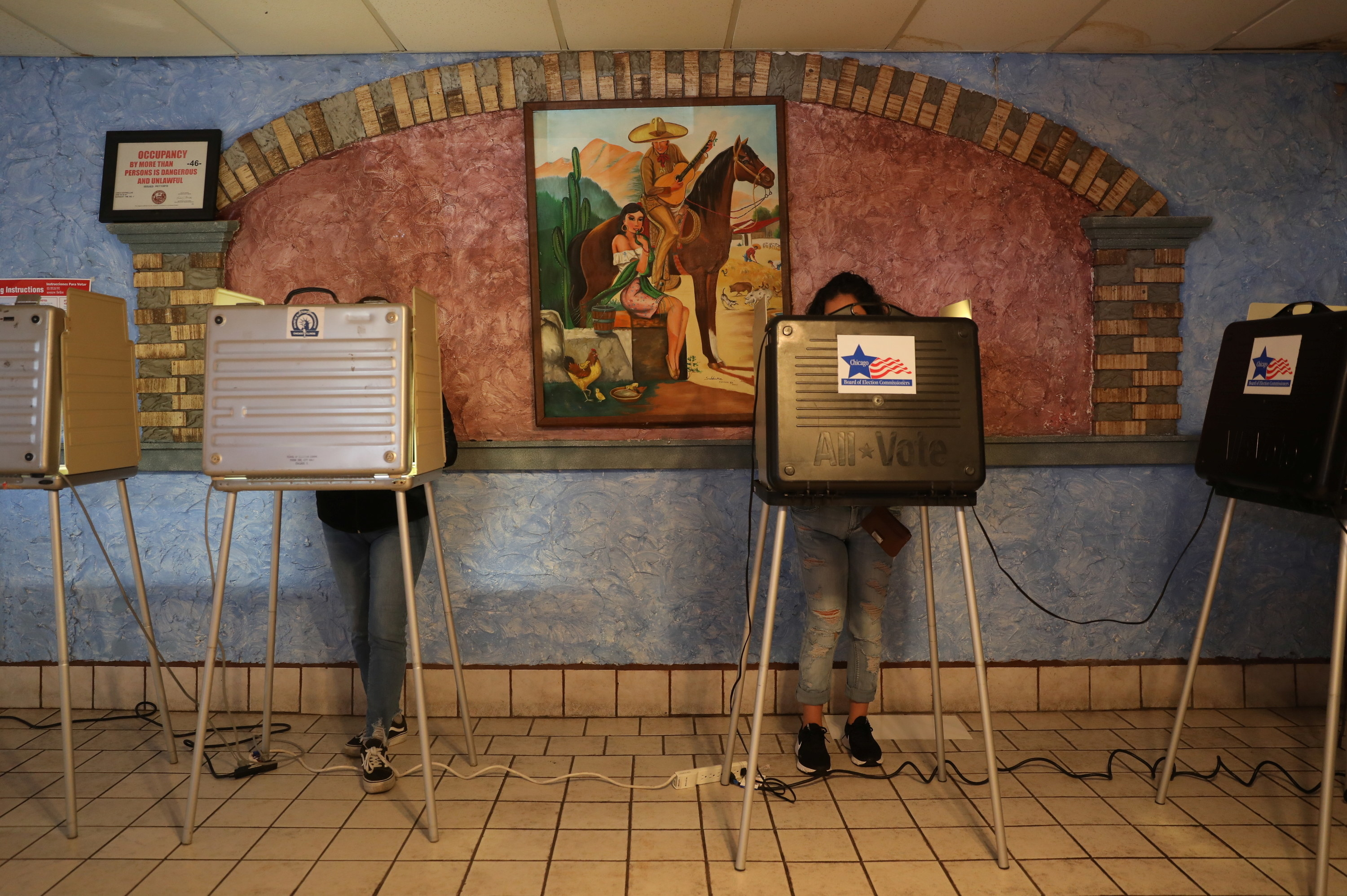 Two people at ballot stations under a mural in a Mexican restaurant.