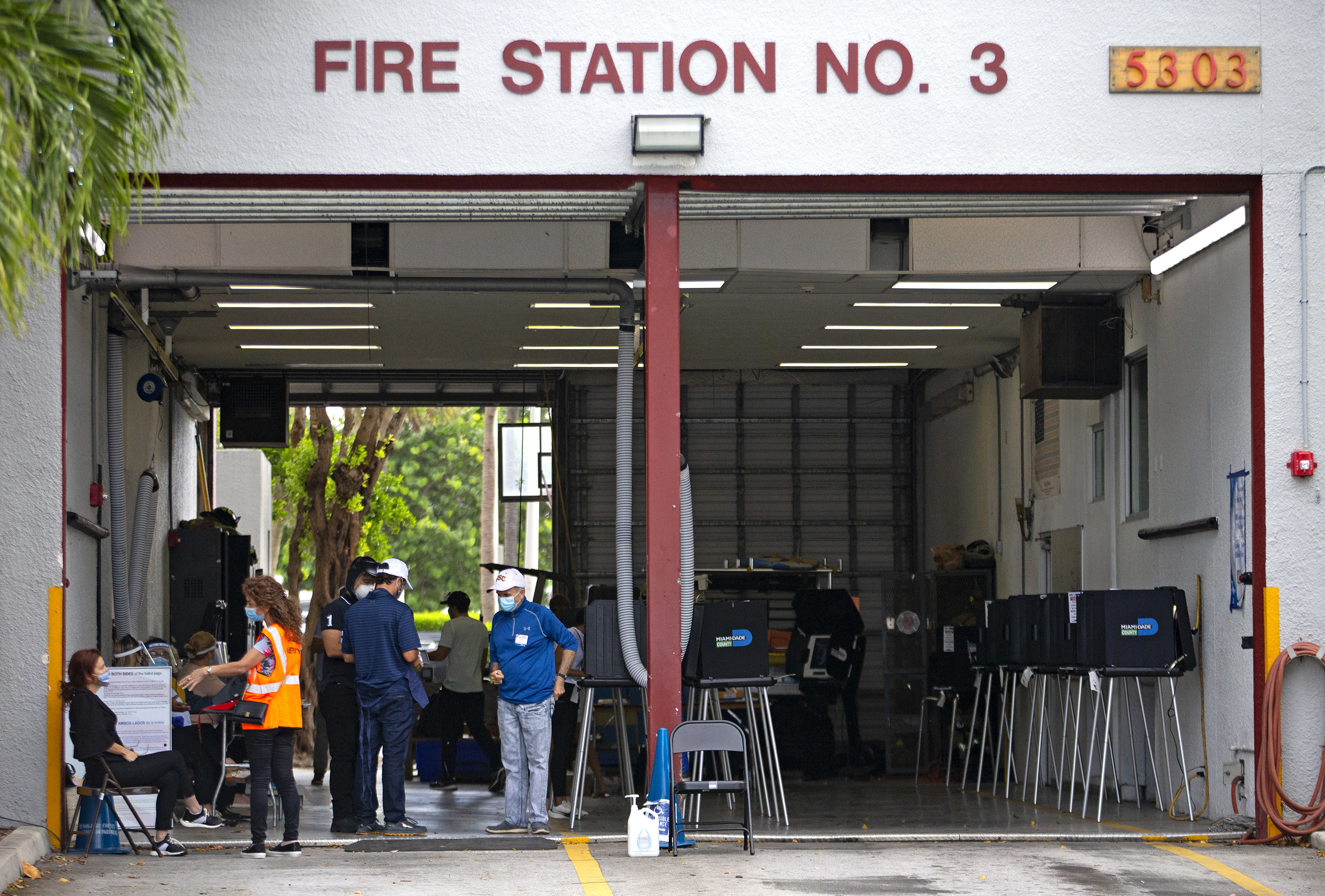 Voters and ballot boxes at a fire station.