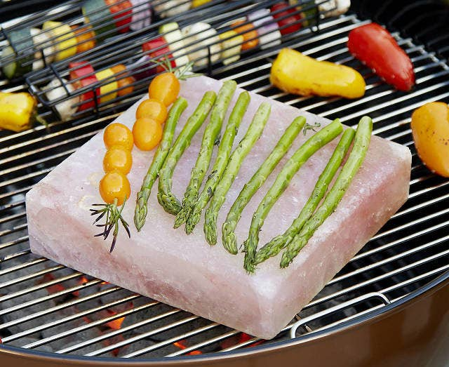 Asparagus and tomatoes lined up on the salt block that's resting on a charcoal grill