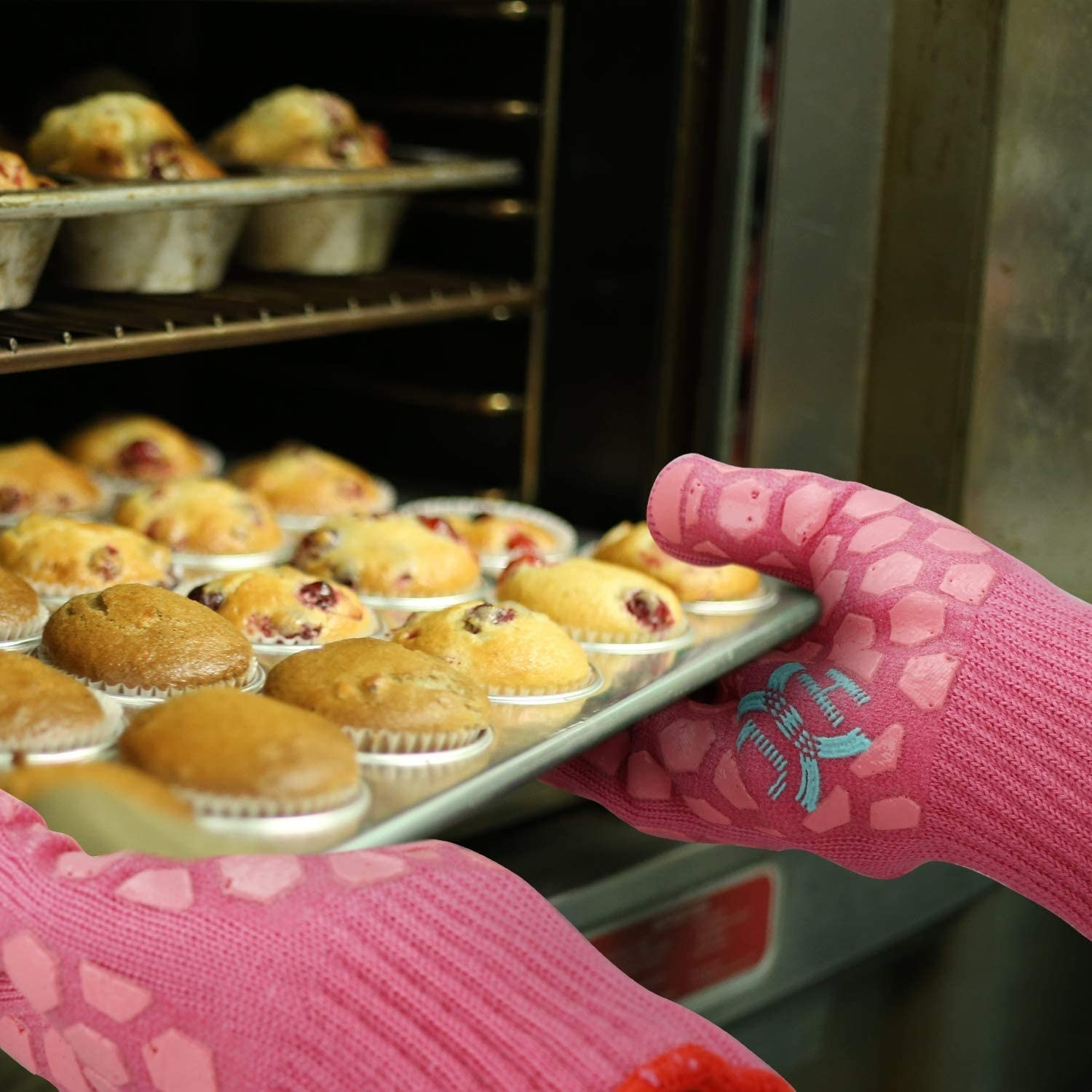 A person wearing the gloves while taking a pan of muffins out of the oven