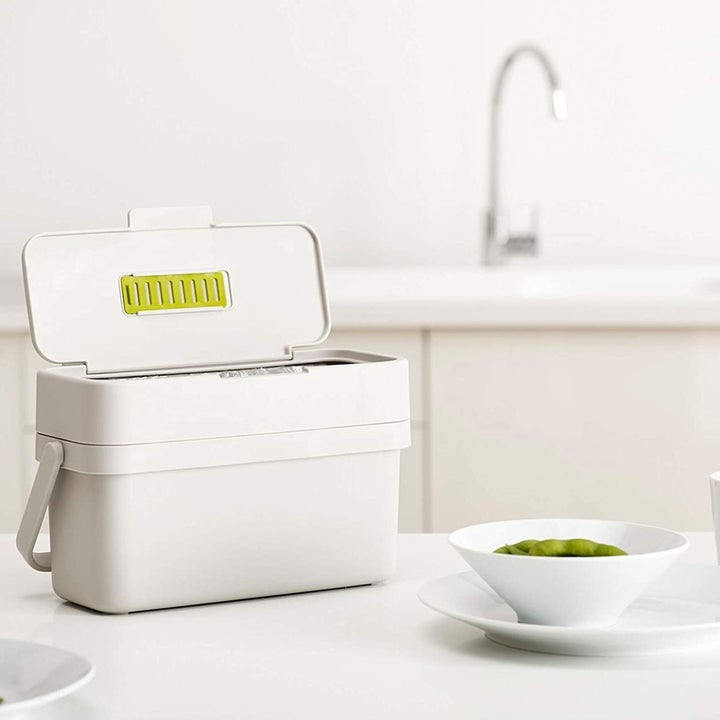 A white compost bin with the lid open sitting on a counter