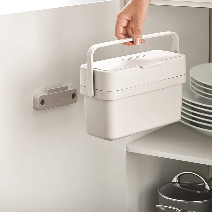 A hand holding a compost bin by the handle moving it towards a wall mount on the inside of a cabinet door