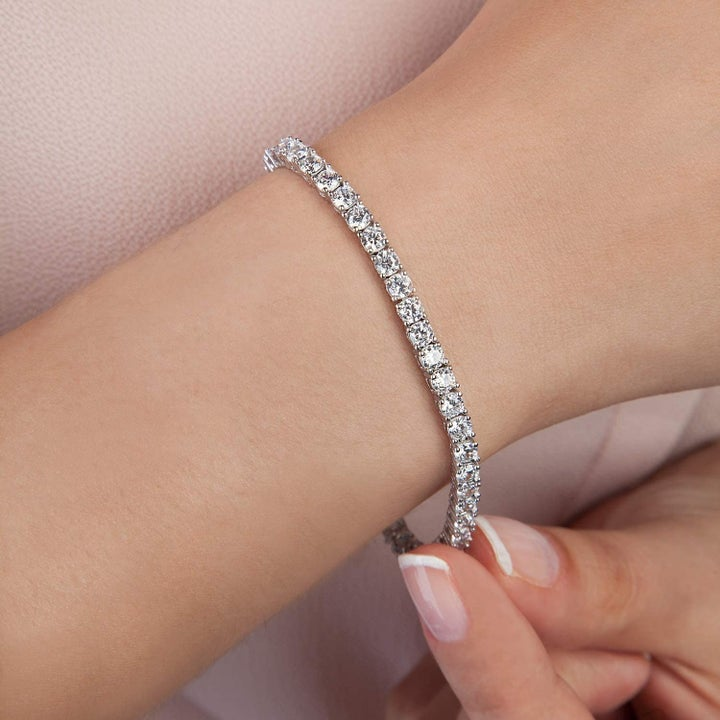 Product shot showing close up of white gold tennis bracelet on model's arm