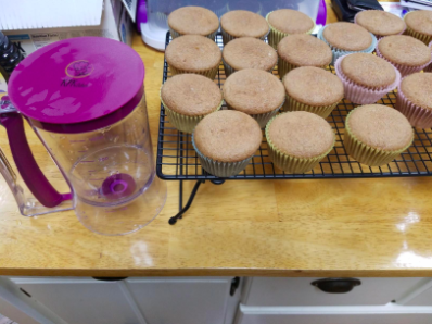 the batter dispenser with cupcakes cooling on a kitchen counter