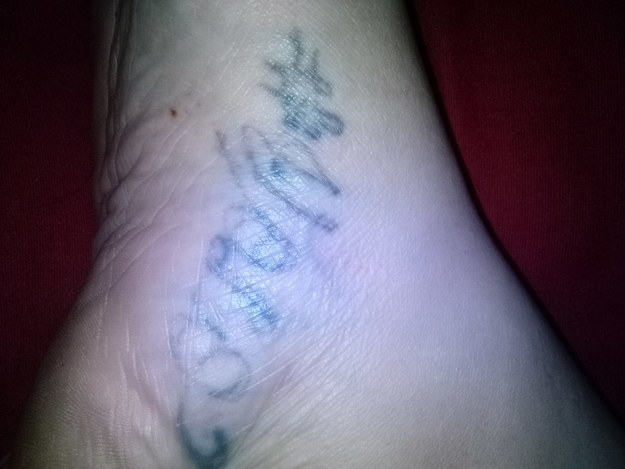 "A very faded tattoo that says, ""#YOLO"" in faded black script on someones ankle"