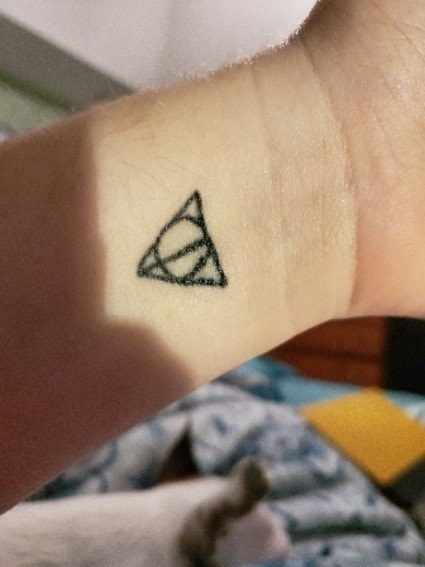 A tattoo of the Deathly Hallows symbol from Harry Potter on someone's wrist in black ink