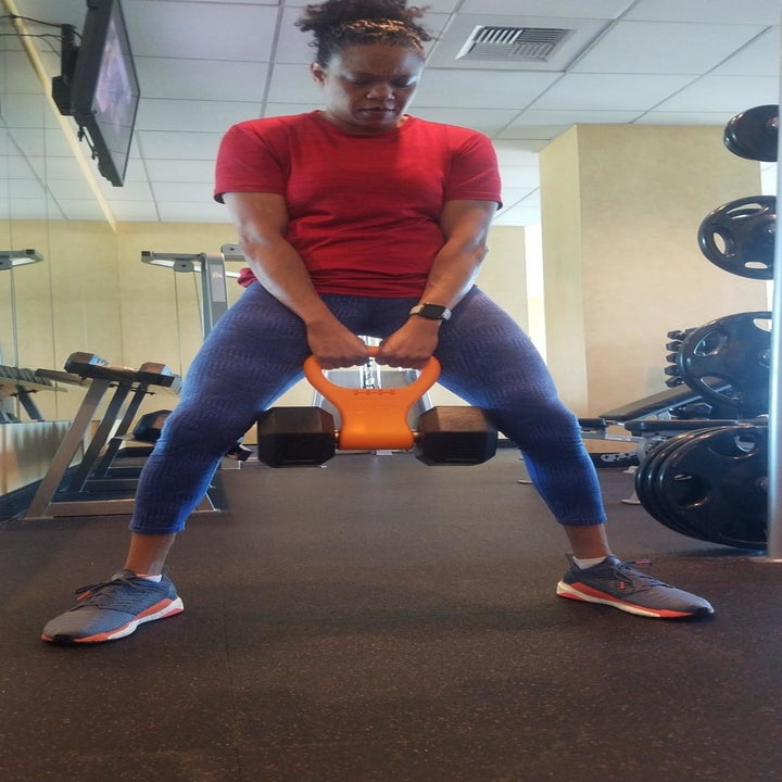 Reviewer squats while holding orange Kettle Gryp wrapped around a weight
