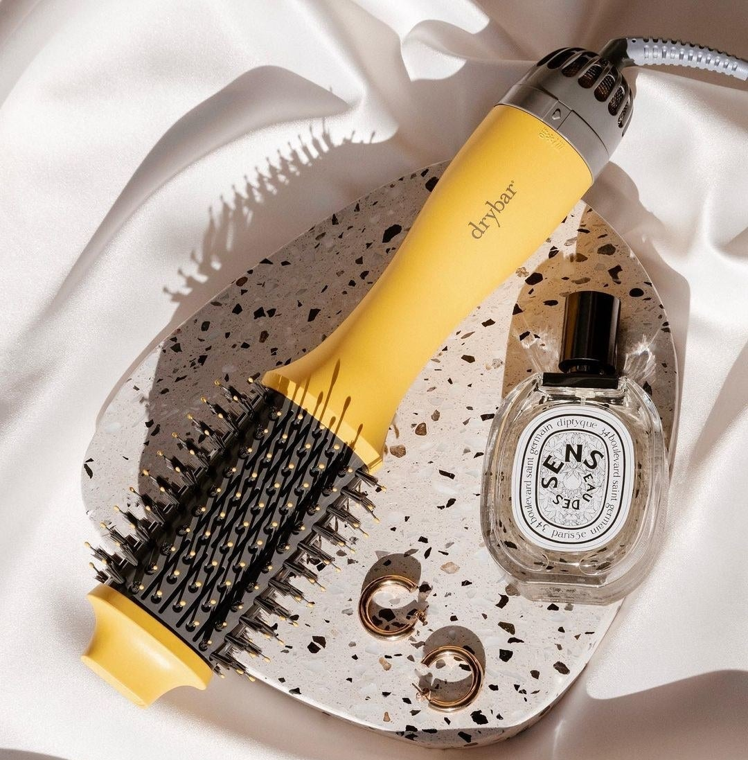 A blow-dry brush next to earrings and perfume on a tray