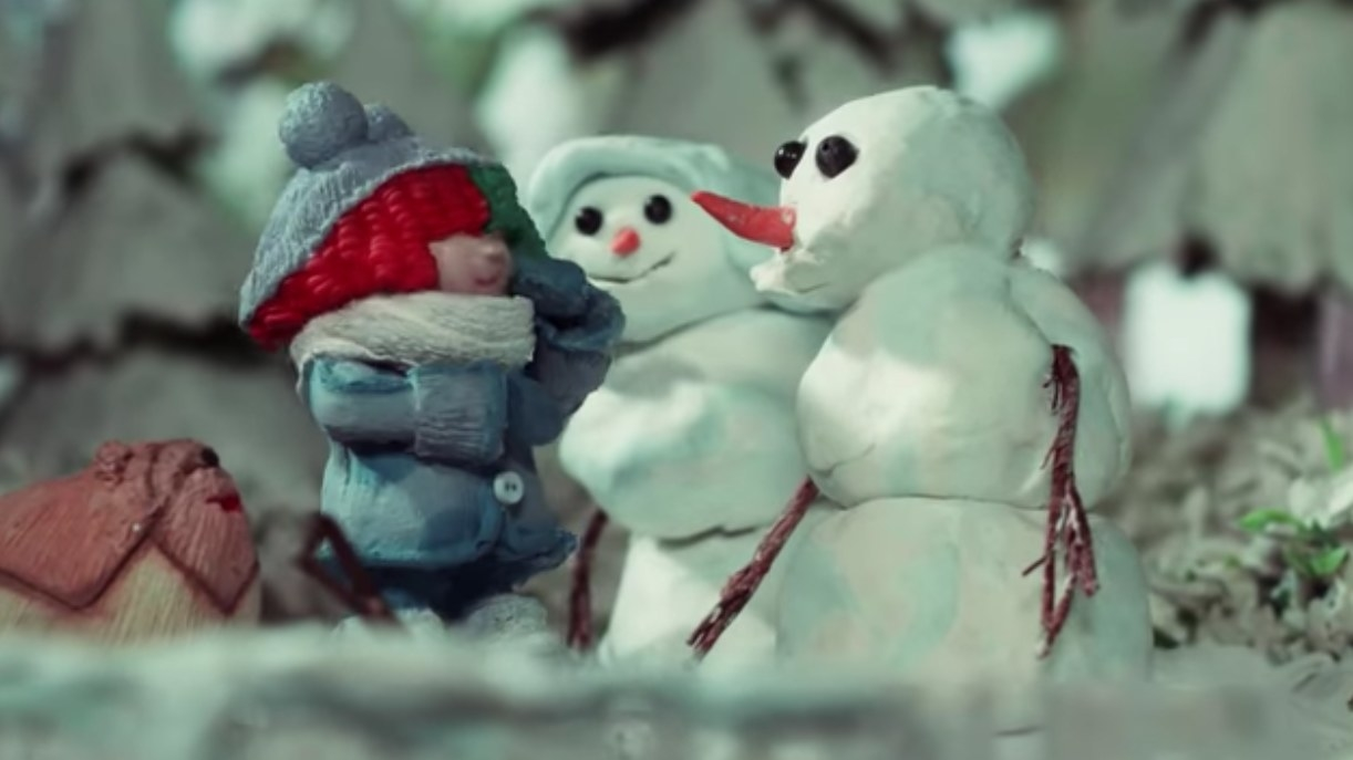 Claymation image of a girl with two snowmen