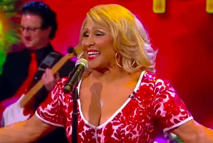 Darlene Love sings in front of a microphone wearing a red and white patterned top