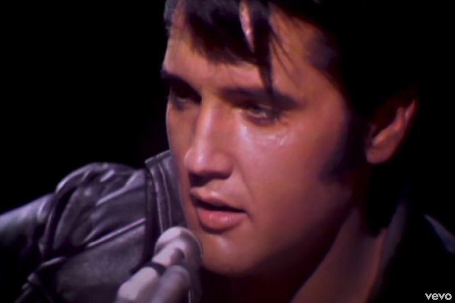 A sweaty Elvis Presley wears a black leather jacket and sings into a microphone