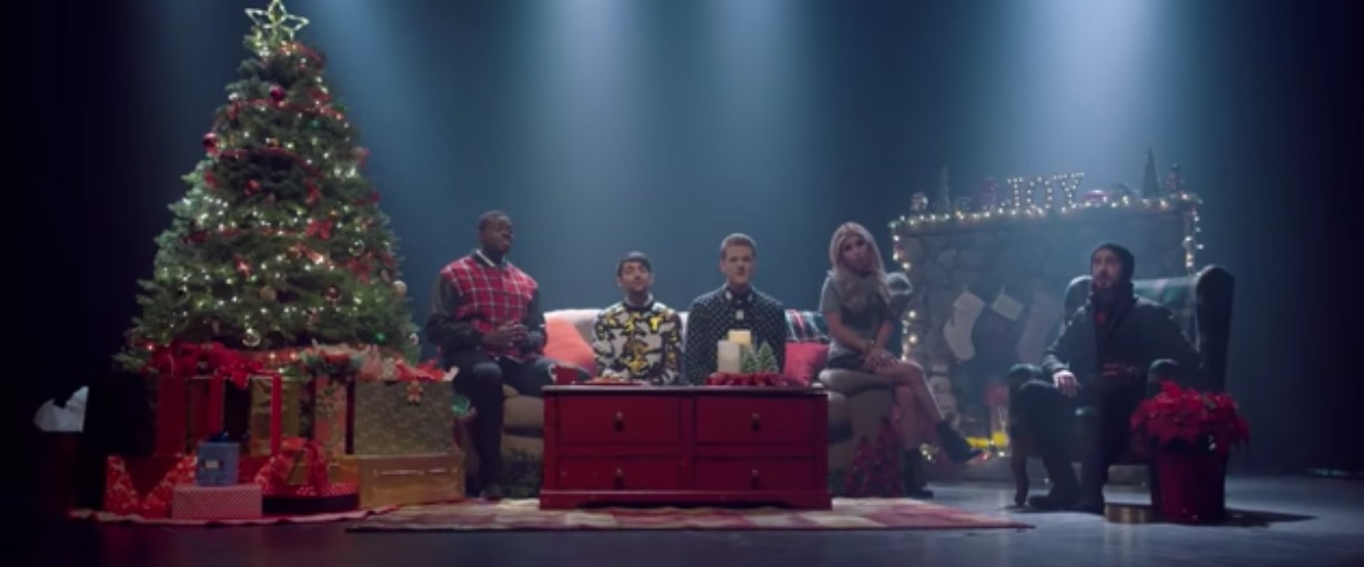 Pentatonix sit in a room decorated for Christmas, with a tree and presents off to the side