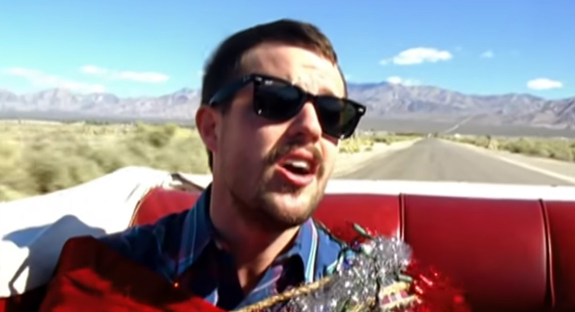 Brandon Flowers sings in the backseat of a convertible with tinsel wrapped around his body