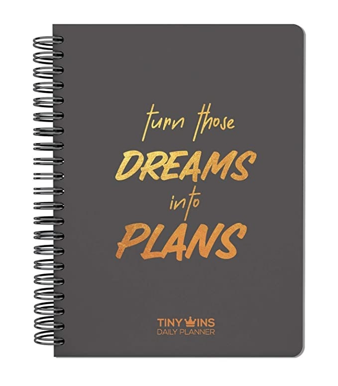 Black spiral planner with the words 'Turn your dreams into plans' printed on it in gold.