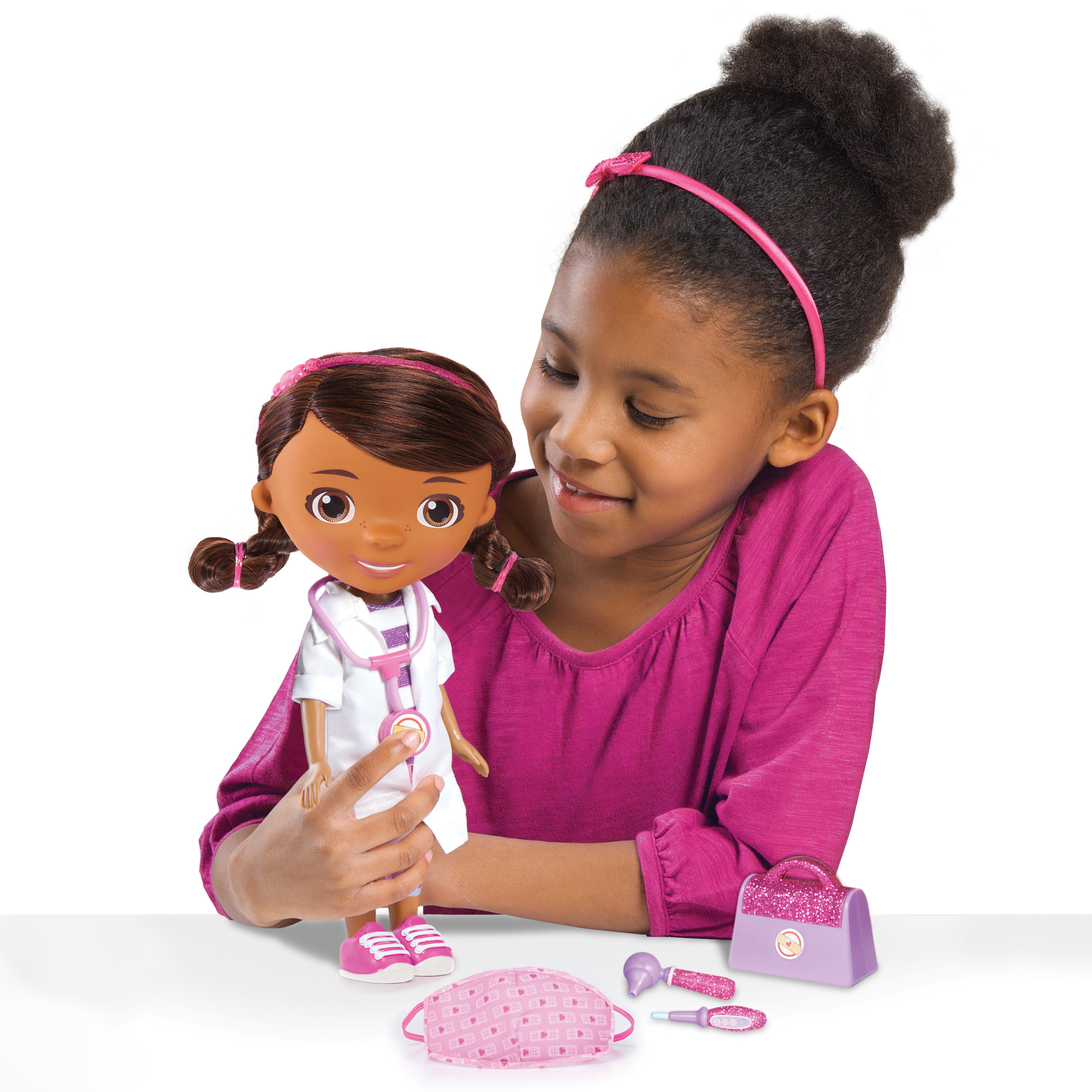child playing with a doc mcstuffins doll and accessories