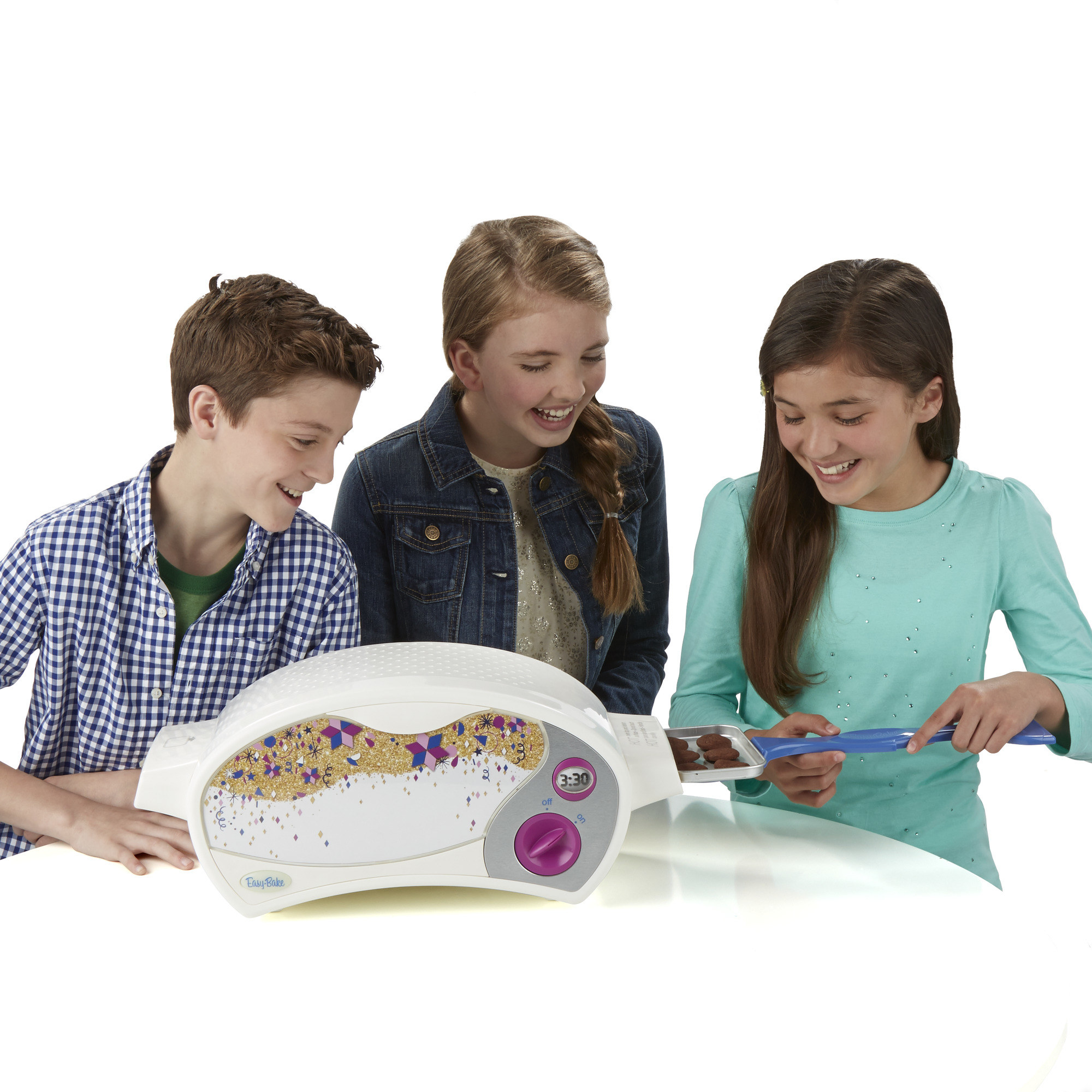 three kids playing with an easy bake oven and putting a tray in
